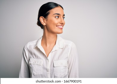 Young beautiful brunette woman wearing casual shirt over isolated white background looking away to side with smile on face, natural expression. Laughing confident.