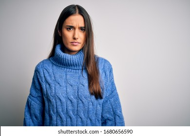 Young beautiful brunette woman wearing casual turtleneck sweater over white background skeptic and nervous, frowning upset because of problem. Negative person.