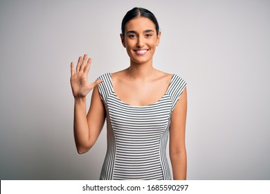 Young beautiful brunette woman wearing casual striped dress over isolated white background showing and pointing up with fingers number five while smiling confident and happy.