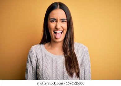 Young beautiful brunette woman wearing white casual sweater over yellow background sticking tongue out happy with funny expression. Emotion concept.