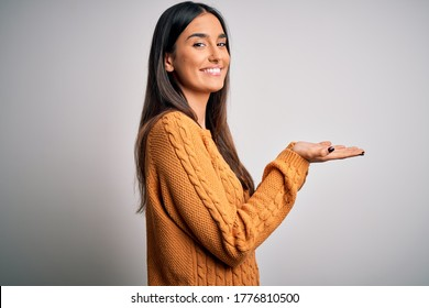 Young beautiful brunette woman wearing casual sweater over isolated white background pointing aside with hands open palms showing copy space, presenting advertisement smiling excited happy