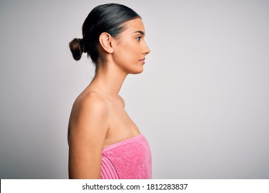 Young beautiful brunette woman wearing towel after shower over isolated white background looking to side, relax profile pose with natural face with confident smile.