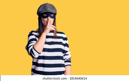 Young beautiful brunette woman wearing burglar mask asking to be quiet with finger on lips. silence and secret concept.