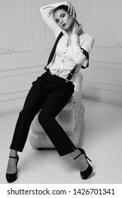 Young beautiful brunette woman in a white shirt with suspenders