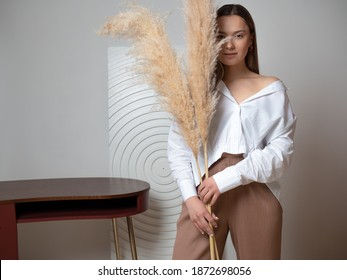 young beautiful brunette woman in a white shirt, a stylish and concise portrait in light colors, a dry spikelet in her hands