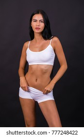 Young beautiful brunette woman in white fitness clothing, isolated on dark gray background