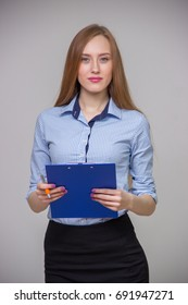 Young beautiful business woman in a blue shirt is holding a document tablet and pen and is thinking on a gray background