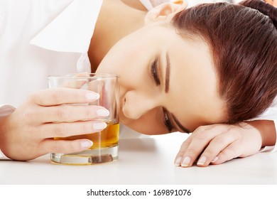 Young beautiful business woman with glass of whiskey or rum. Isolated on white.