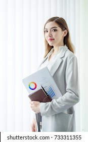 Young Beautiful Business Woman holding financial Document Papers in White Modern Office Room