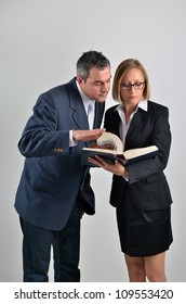 Young beautiful business woman with male colleague reading a book