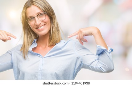 Young beautiful business woman over isolated background looking confident with smile on face, pointing oneself with fingers proud and happy.