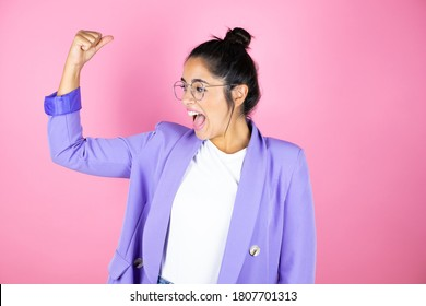 Young beautiful business woman over isolated pink background showing arms muscles smiling proud