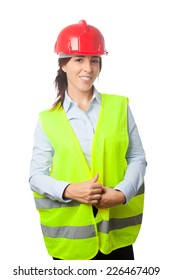 Young beautiful business woman over white background. Smiling wearing a red helmet and work vest
