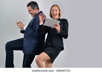Young beautiful business woman playing with a tablet and male colleague playing with a phone