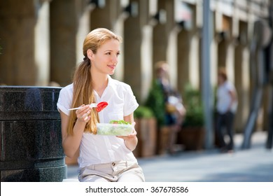 Young beautiful business woman sitting on the city street and having lunch. Eating salad on lunch break and drinking coffee.  Living healthy lifestyle. Happy smile.