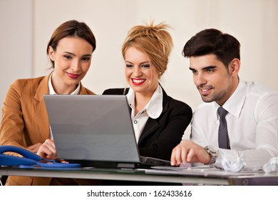 Young beautiful business woman smiling with a laptop in front of her and two colleagues business people in the back