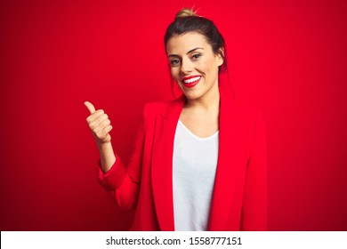 Young beautiful business woman standing over red isolated background smiling with happy face looking and pointing to the side with thumb up.