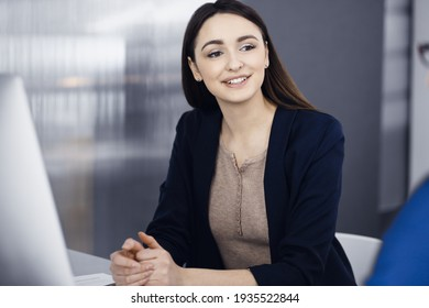 Young beautiful business woman is talking to her colleague, while sitting at the desk in a modern office. Concept of business success