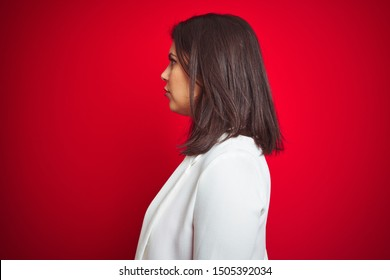 Young beautiful business woman wearing elegant jacket over red isolated background looking to side, relax profile pose with natural face with confident smile.