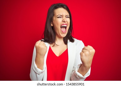 Young beautiful business woman wearing elegant jacket over red isolated background very happy and excited doing winner gesture with arms raised, smiling and screaming for success. Celebration concept.