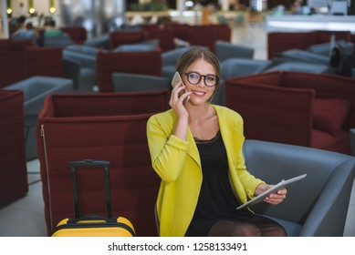 Young beautiful business woman with a yellow suitcase in the airport lounge uses a smartphone and tablet.