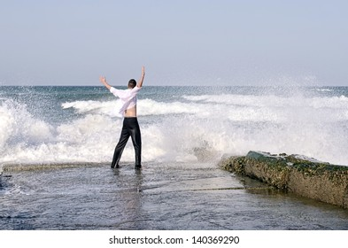 Young beautiful businessman enjoying his time on a beach while waves are hitting the shore