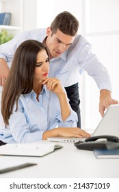 Young beautiful businesswoman and businessman discussing and working in the office