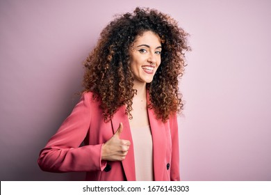 Young beautiful businesswoman with curly hair and piercing wearing elegant jacket doing happy thumbs up gesture with hand. Approving expression looking at the camera showing success.