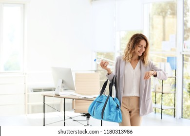 Young beautiful businesswoman holding fitness bag in office. Space for text