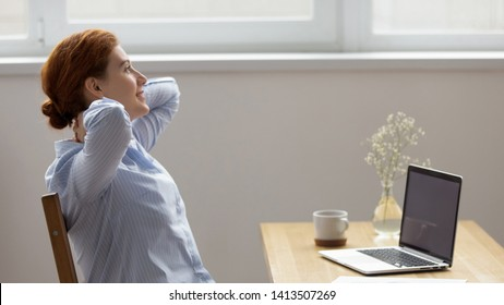 Young beautiful businesswoman lean back holding arms behind head having rest. Calm female in office at work take break looking out window. Harmony stress free dreams visualization relaxation concept