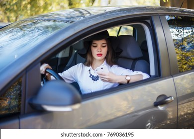 A young beautiful businesswoman is looking on her smart phone while sitting in her car