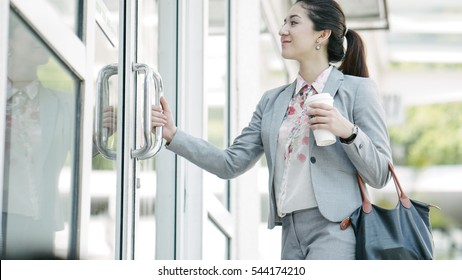 Young beautiful businesswoman opening the door with coffee