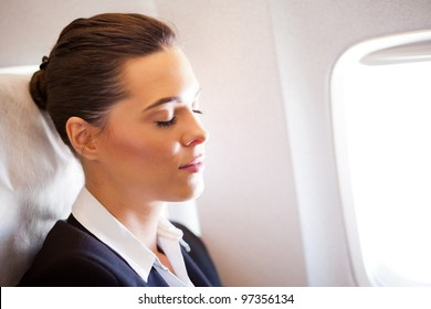 young beautiful businesswoman resting on airplane