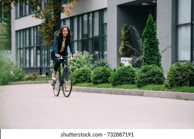 young beautiful businesswoman riding bicycle