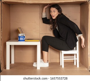 young beautiful businesswoman sitting in office cardboard box, tomfoolery around at work
