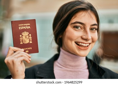 Young beautiful businesswoman smiling happy holding spainish passport at the city.