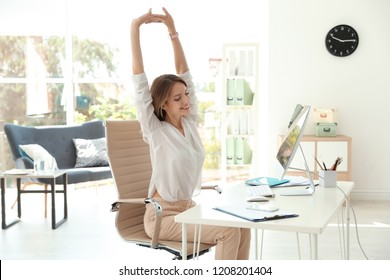 Young beautiful businesswoman stretching in office. Workplace fitness