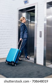 young beautiful businesswoman with suitcase entering elevator