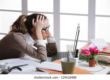 Young and beautiful businesswoman tired from work in the office.Woman holding her head