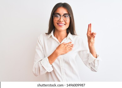Young beautiful businesswoman wearing glasses standing over isolated white background smiling swearing with hand on chest and fingers up, making a loyalty promise oath