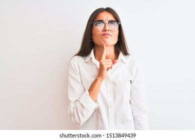Young beautiful businesswoman wearing glasses standing over isolated white background Thinking concentrated about doubt with finger on chin and looking up wondering