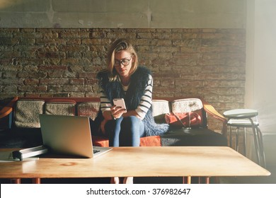 young beautiful businesswoman writes a message on her smart-phone during the lunch break. Attractive female student doing homework in a coffee-shop