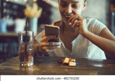 young beautiful businesswoman writes a message on her smart-phone during the lunch break. Attractive female student doing homework in a coffee-shop, food chocolate, happy face, closeup hipster