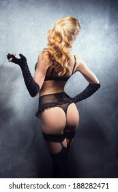 Young and beautiful cabaret dancer in sexy vintage lingerie smoking cigar over retro background
