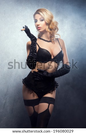 d9fcf9b2e30 Young and beautiful cabaret dancer in sexy vintage lingerie smoking cigar  over retro background