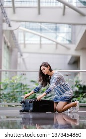 A young, beautiful and casually dressed Indian Asian woman is kneeling and packing her luggage in the airport. She is organizing her items to check in her luggage to go for a holiday.