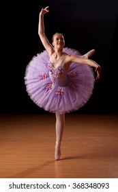 Young beautiful caucasian ballerina practicing in studio
