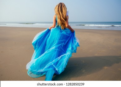 Young beautiful caucasian blonde woman in long tull butterfly white blue dress on coast of sea.female running towards the ocean freedom