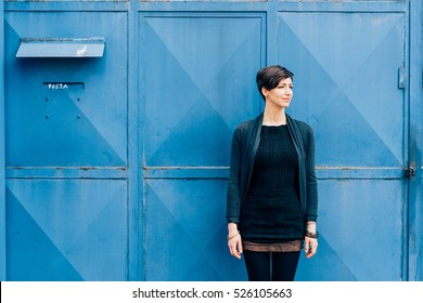Young beautiful caucasian brown hair woman posing outdoor in the city, looking over pensive leaning on blue wall - serious, melancholy, serene concept