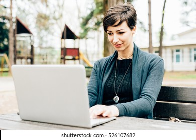Young beautiful caucasian brown hair woman sitting on a bench in a park using computer and smart phone â?? technology, multitasking, business concept
